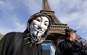 anonymous mask outside Eiffel Tower
