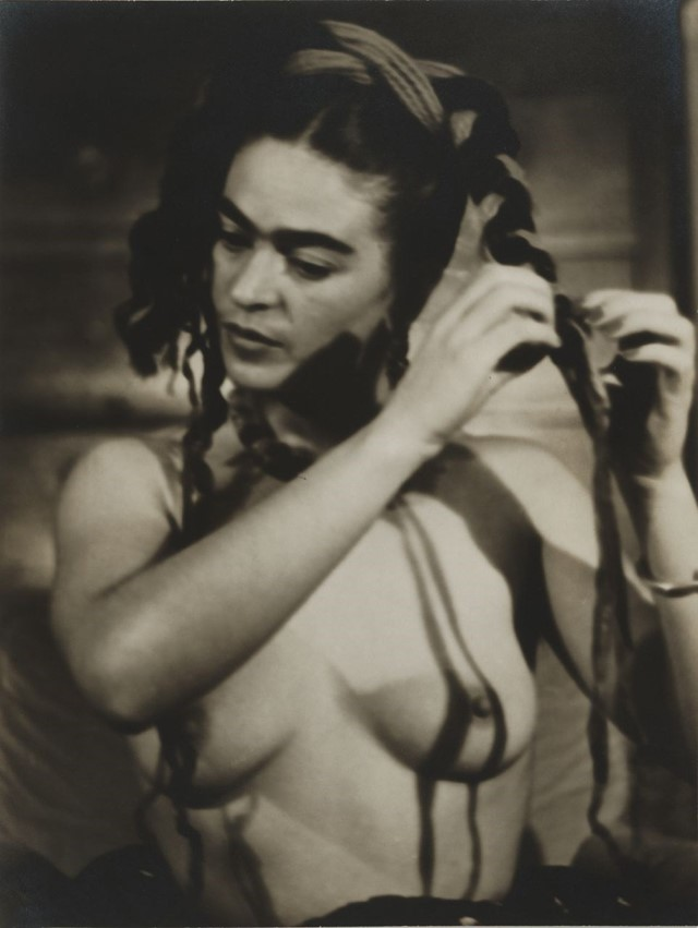Frida Kahlo braiding her hair