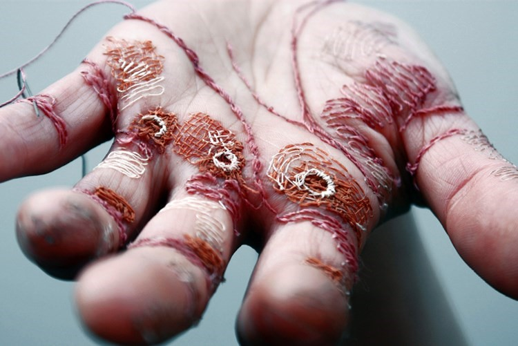 This artist is stitching her own hand with needle and ...