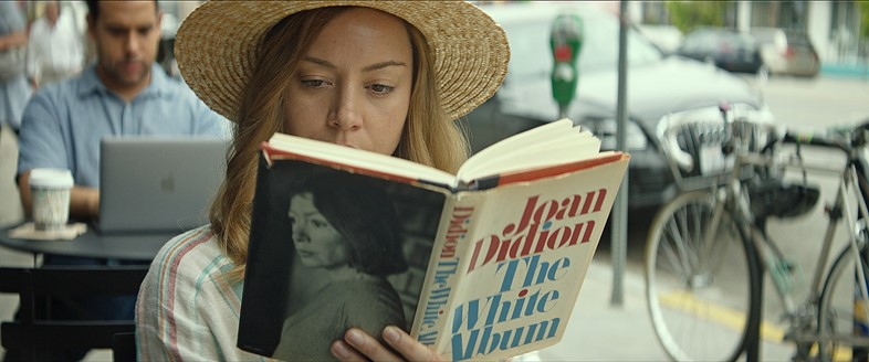 Ingrid (Aubrey Plaza) reads in a public place in I